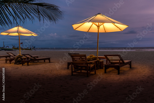 Fotobehang Bali Umbrellas and sunbeds on the beach at night