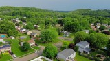 A slowly rising aerial establishing shot of a typical Pennsylvania residential neighborhood on a sunny summer day. Pittsburgh suburbs.  	 - 206702286