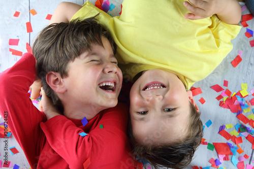 Foto Murales niños tumbados sobre confetti riendo en una fiesta de cumpleaños