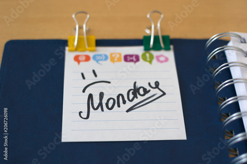 the name of the day of the week written on a sticky sheet in a blue notebook with springs