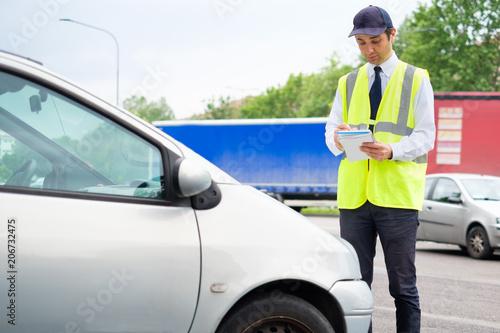 Leinwanddruck Bild Parking officer writing parking charge notice time limit