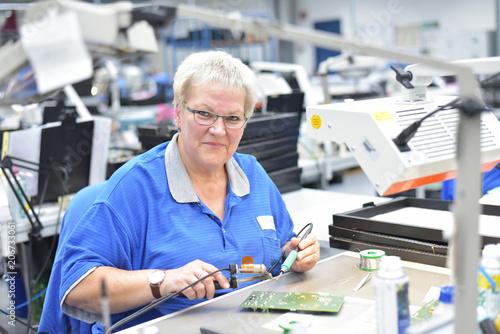 canvas print picture Portrait ältere Frau in einer Fabrik zur Montage von moderner Elektronik am Arbeitsplatz // older woman in a factory to assemble modern electronics at the workplace