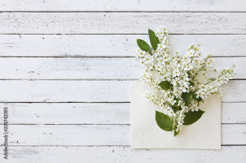Close-up of envelope with beautiful flowering tree branches on white wooden background. Top view