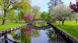 Scenic stone bridge reflected in tranquil waters, with blossoming trees.