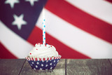 Patriotic 4th of July celebration cupcake with a candle. The American flag in the background. Vintage tone. - 206773828