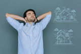 Pleasant dreams. Young tired man closing his eyes and feeling good while dreaming about owning a beautiful house - 206776498