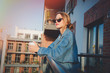 Young redhead girl in jeans clothes and cup of coffee standing on balcony alone. - 206807288