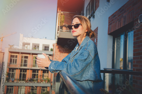 Young redhead girl in jeans clothes and cup of coffee standing on balcony alone.