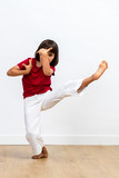 concentrated young child showing grace with fighting legs and arms - 206812817