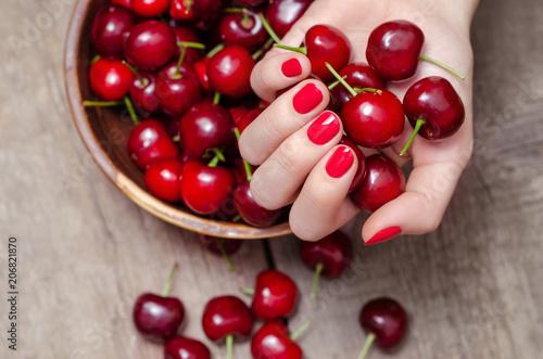 Fotobehang Kersen Female hand with red nail design holding fresh cherries