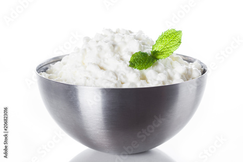 Fresh cottage cheese in a metal bowl isolated on white background. Close up