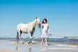 Girl walking on the beach with white horse.