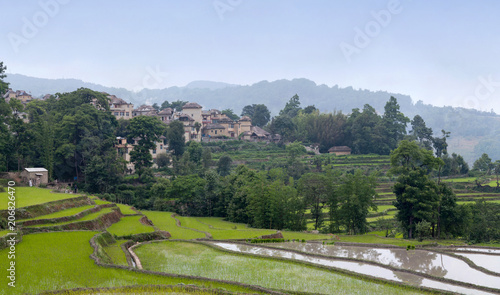 Fotobehang Rijstvelden Village over terraced rice fields in Yuanyang, Yunnan Province of China