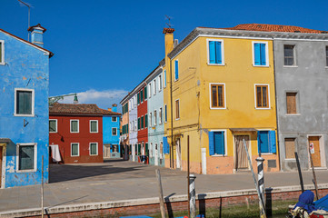 Overview of colorful buildings and clothes hanging in a blue sunny day, in front of a canal at Burano, a gracious little town full of canals, near Venice. Located in the Veneto region, northern Italy © Celli07