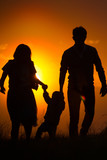 Parents with a baby have fun on the background of sunset with their hands up - silhouette - 206834423