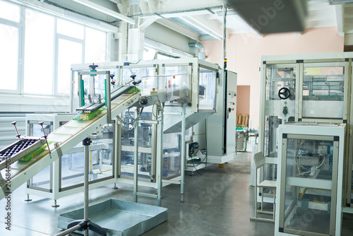 Interior of production workshop at food factory, modern assembly line units for packaging, copy space