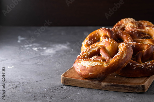 Sticker Freshly baked homemade soft pretzel with salt on rustic table. Perfect for Octoberfest.