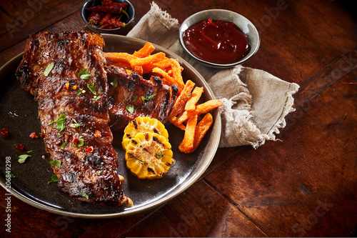 Portion of spicy barbecued spare ribs with veggies