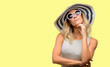 Leinwanddruck Bild - Young woman wearing sunglasses and summer hat thinking and looking up expressing doubt and wonder