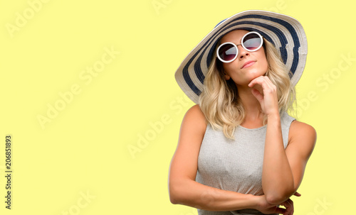 Leinwanddruck Bild Young woman wearing sunglasses and summer hat thinking and looking up expressing doubt and wonder