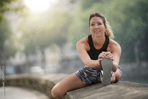 Foto Murales Athletic woman stretching out after running