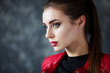 Portrait of beautiful girl with perfect red lips wearing red jacket.