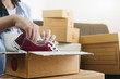 Leinwanddruck Bild - Happy young businessman owner packing shoes to cardboard box, Young Owner Woman Start up for Business Online. People with online shopping SME entrepreneur or freelance working concept.