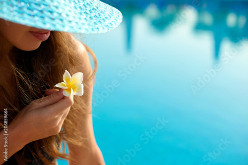 Woman in a straw hat relaxing on a deck-chair near a luxurious summer pool in hotel, concept time to travel
