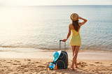 Beautiful young woman with a hat standing with suitcase on the wonderful sea background, concept of time to travel