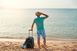 Man tourist in summer clothes with a suitcase in his hand, looking at the sea on the beach, concept of time to travel