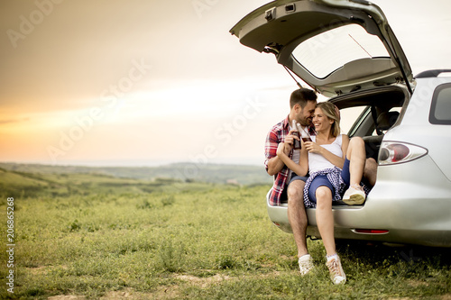 Loving couple sitting in the car trank