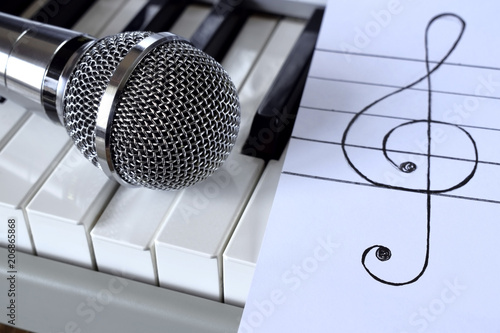 Synthesizer, microphone and treble clef on white paper - 206865868