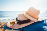 Sun hats and glasses on beach in the sand by the water - 206880007