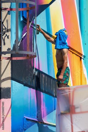 Fotobehang Graffiti Graffiti- Künstler während der Arbeit auf einem verlassenen Firmengelände