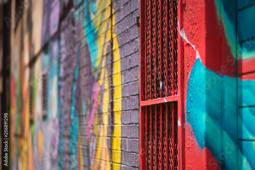 Abstract shot of colorful graffiti details on a brick wall and gate in Johannesburg CBD - 206891298