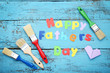 Inscription Happy Fathers Day with paintbrush on wooden table