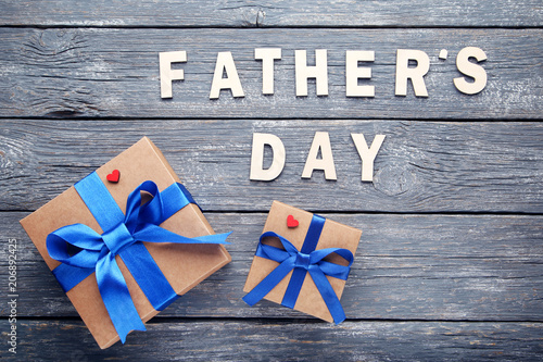Foto Murales Inscription Fathers Day with gift boxes on wooden table