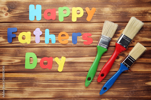 Inscription Happy Fathers Day with paintbrush on brown wooden table