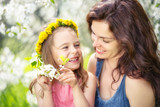 Mother and daughter in spring cherry blossom park - 206895837