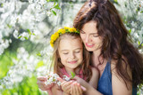 Mother and daughter in spring cherry blossom park - 206895880