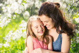 Mother and daughter in spring cherry blossom park - 206896020