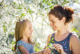 Mother and daughter in spring cherry blossom park - 206896264