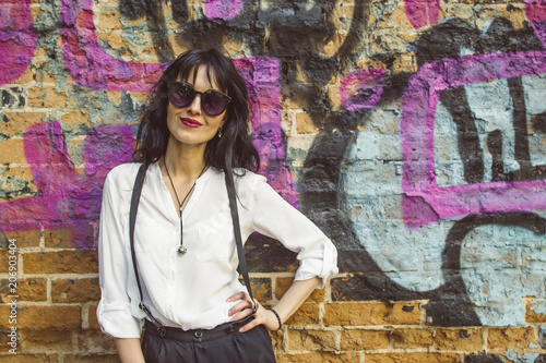 Stylish young woman on graffiti background. Portrait of a fashionable female in sunglasses.