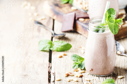 Canvas Milkshake Chocolate-mint creamy smoothies in bottles on an old wooden background, selective focus