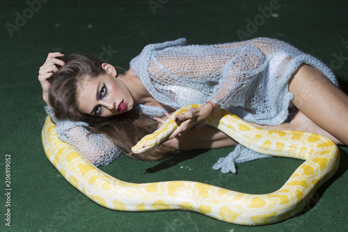 Sexy young woman posing with albino python against green background © tverdohlib