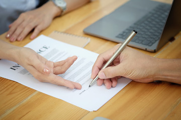 Man signing a car insurance policy, the agent is pointing the document © bongkarn