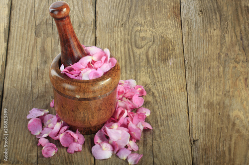petals of rose in martar on wooden background