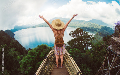 Foto Murales Happy female hiker standing on a cliff with her arms up in the air feeling free
