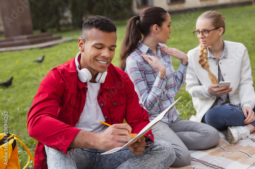 Fashionable student. Fashionable student wearing red jacket feeling happy while sitting near girls in the park