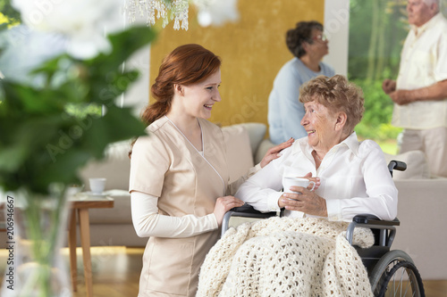 Smiling nurse taking care of happy paralysed senior woman in the nursing house